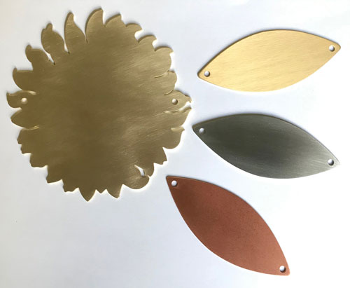 sunflower and leaf plaques in gold, silver & bronze.